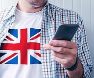 a man in t-shirt with Great Britan flag hold smartphone in his hand